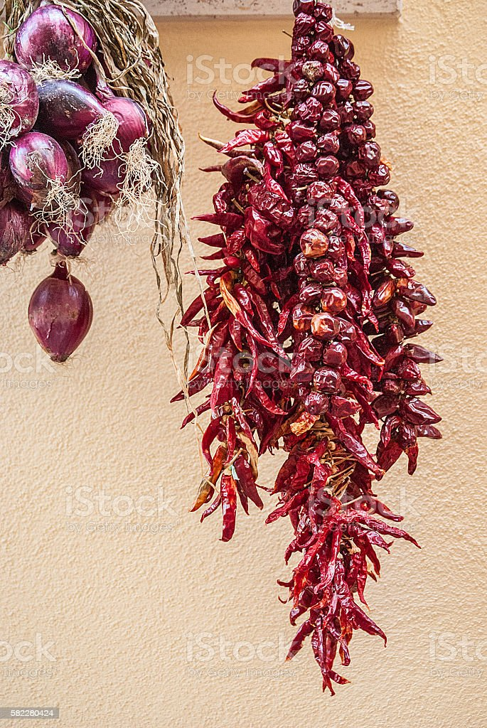 Bundles of red onion and red hot peppers hanging stock photo