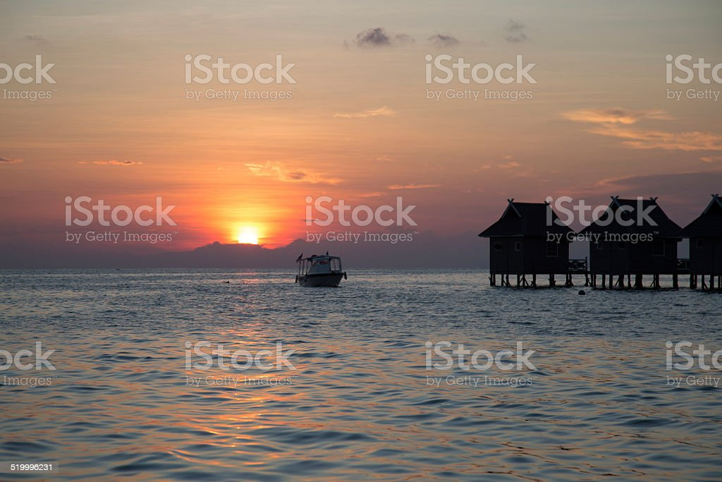 Bungalow on the ocean with sunset background. stock photo