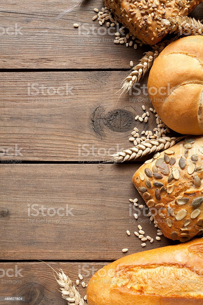 Buns and wheat ears on old wooden table stock photo
