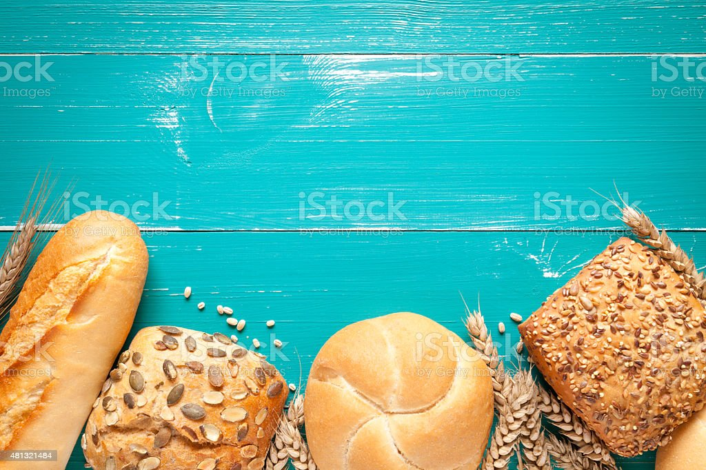Buns and wheat ears on turquoise table stock photo