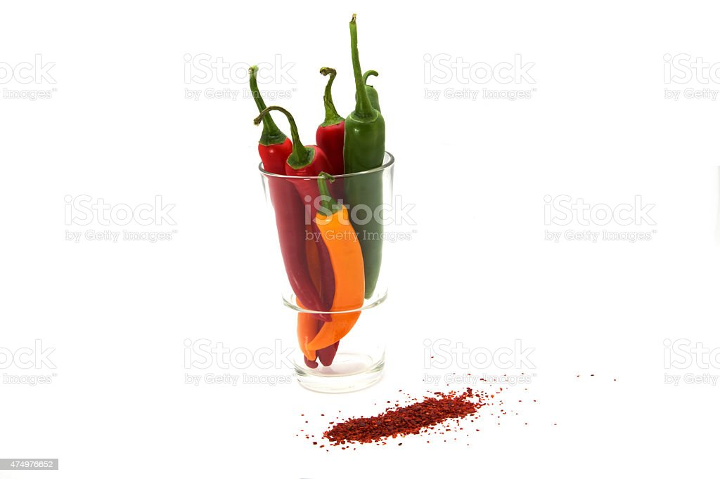 Bunte Chilis im Glas mit Chiliflocken stock photo