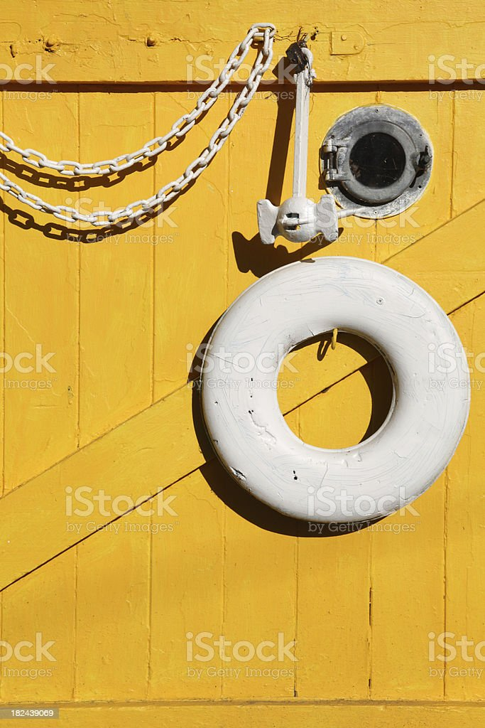 buoy and anchor hanging on yellow wall royalty-free stock photo