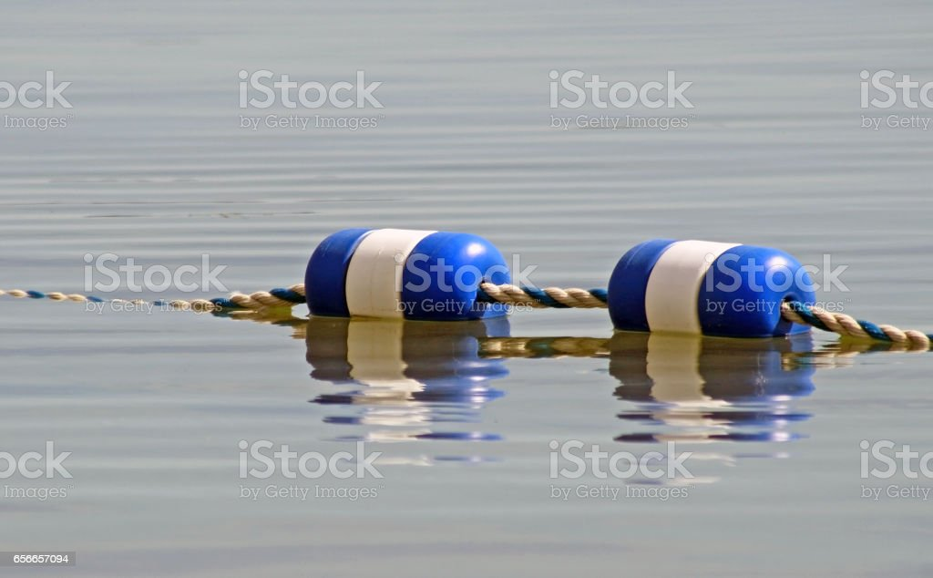 Buoys strung together and floating on surface of water stock photo