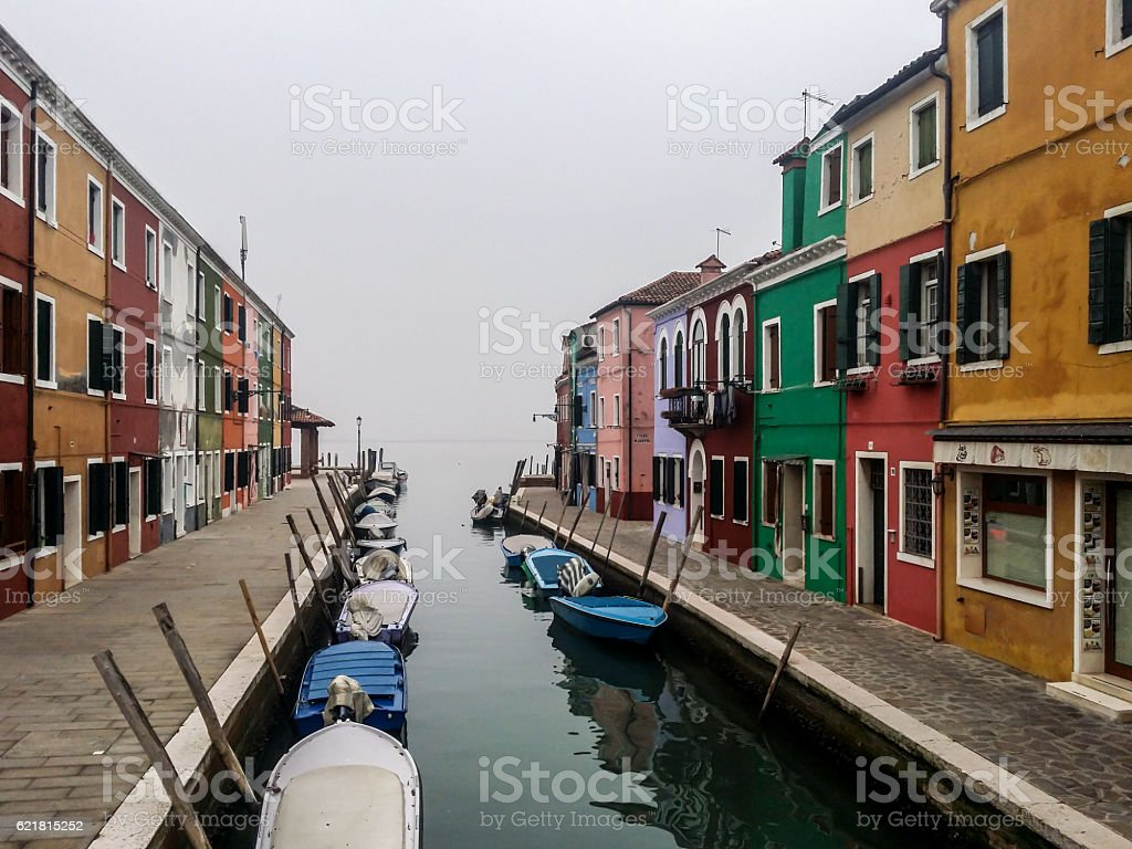 Burano island canal with boats and colorful buildings stock photo