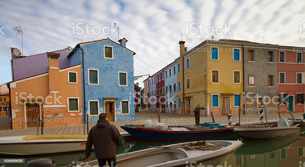Burano, Venice: Men with Boats on Canal Near Colorful Homes stock photo