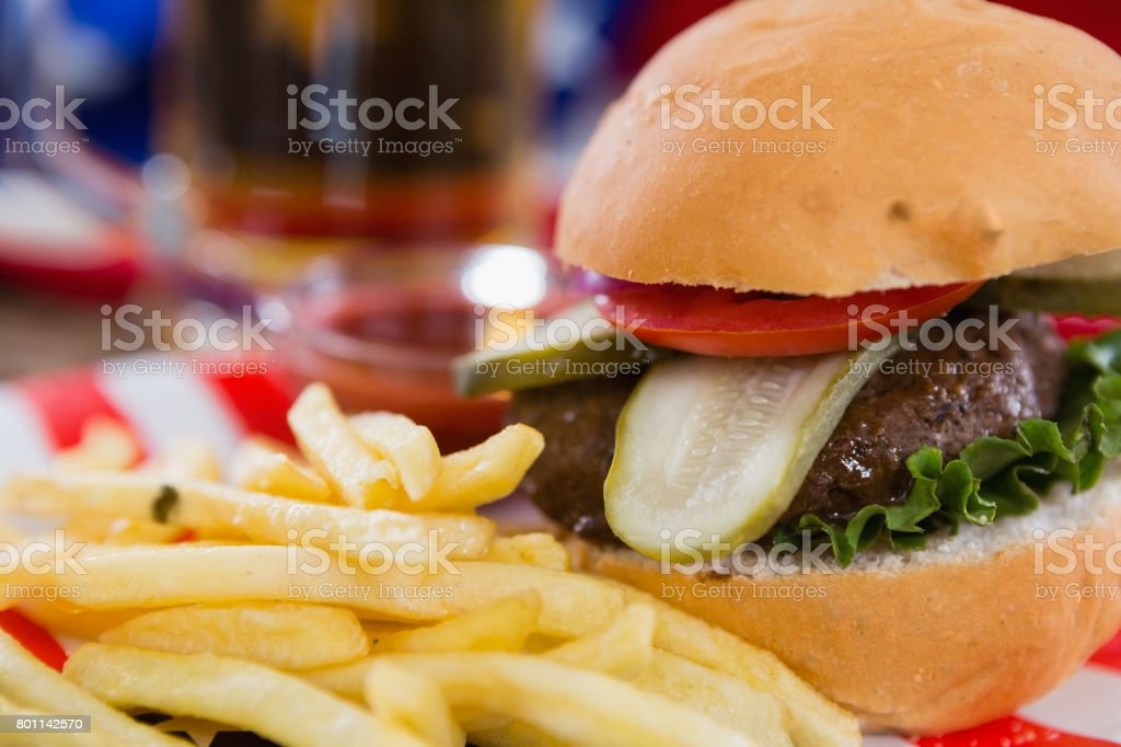 Burger and french fries on wooden table with 4th july theme stock photo
