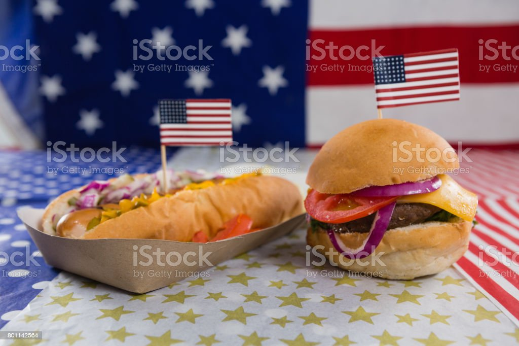 Burger and hot dog on wooden table with 4th july theme stock photo