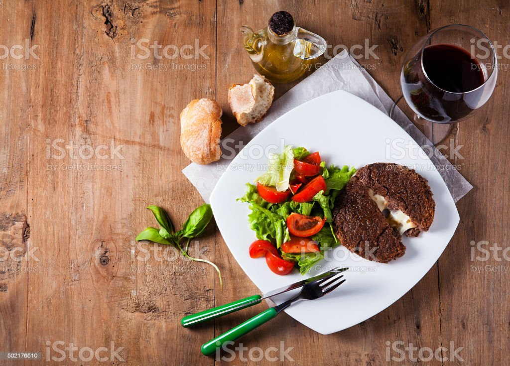 Burger cutlet stuffed with cheese inside of legumes with vegetab stock photo