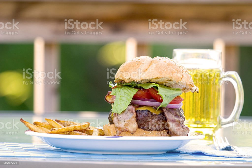 Burger, fries and beer on the deck royalty-free stock photo