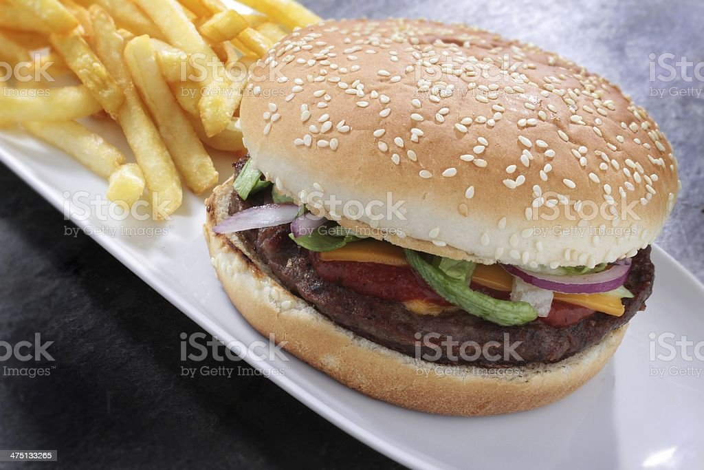 burger in seeded bun with fries and salad stock photo