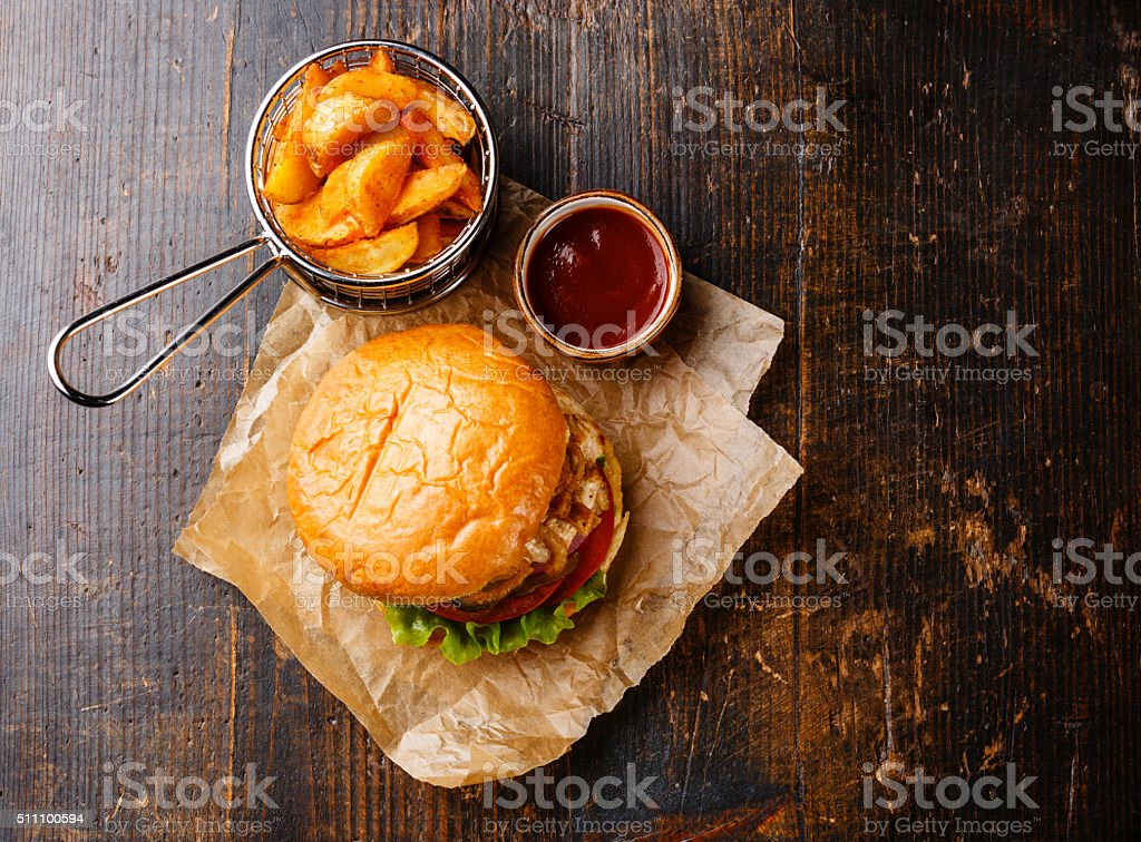 Burger with chicken breast and fried onions with potato wedges stock photo