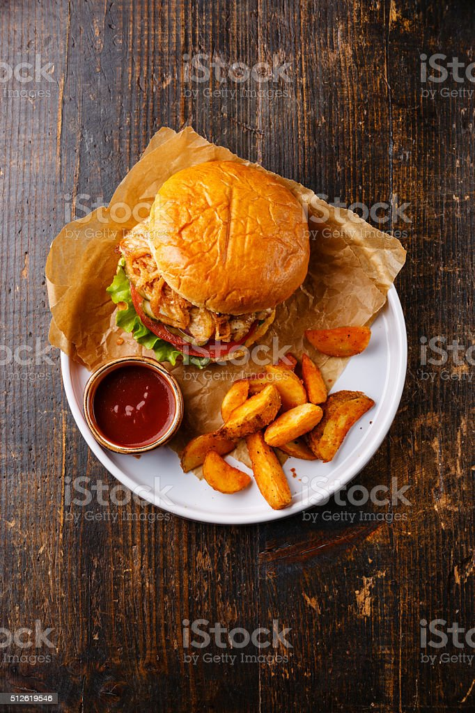 Burger with chicken breast and potato wedges on plate stock photo