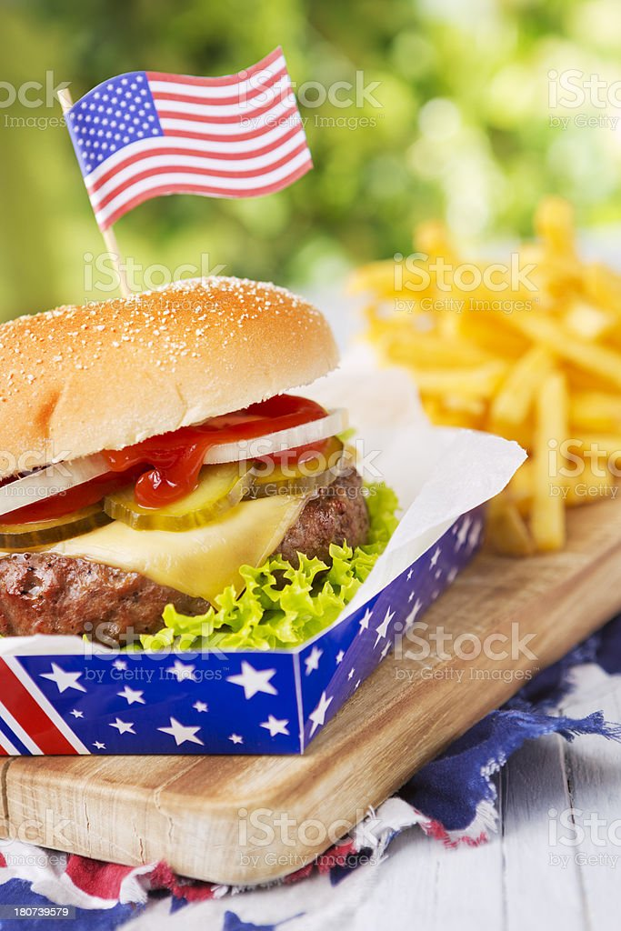 Burger with fries on an outdoor table in bright light royalty-free stock photo