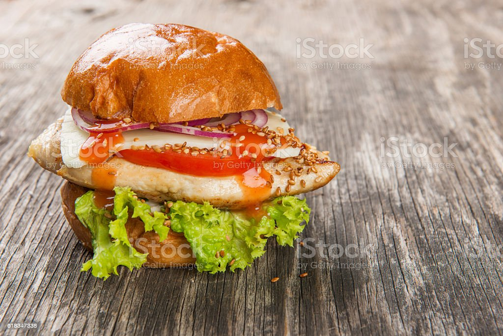 Burger with grilled chicken on rustic wooden table stock photo