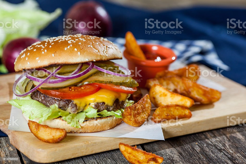 burger with meat and vegetables on a wooden background stock photo