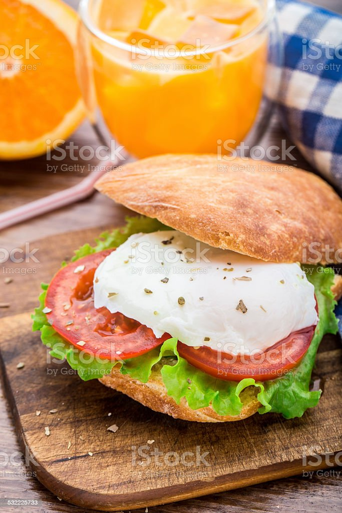 Burger with pouched egg and tomato stock photo
