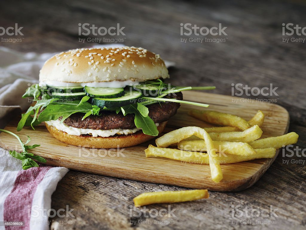 Burger with sprouts and cucumber on cutting board with fries royalty-free stock photo