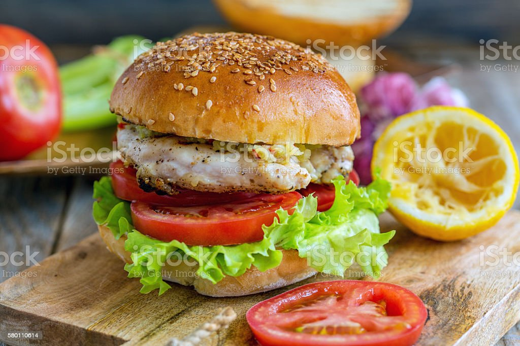 Burger with vegetables, chicken and spicy sauce. stock photo
