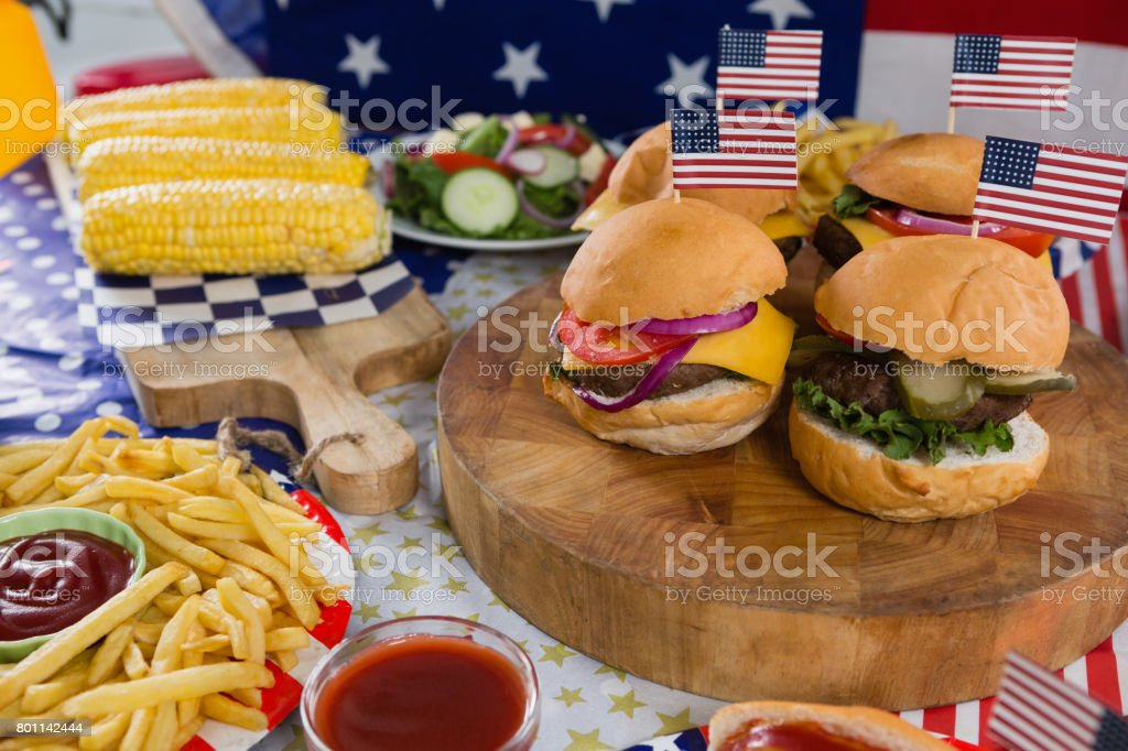 Burgers and corn cob on wooden table with 4th july theme stock photo