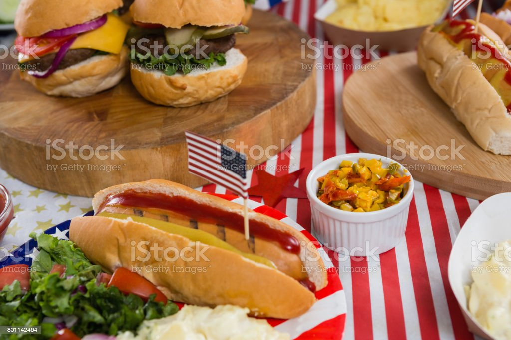 Burgers and hot dogs on wooden table with 4th july theme stock photo