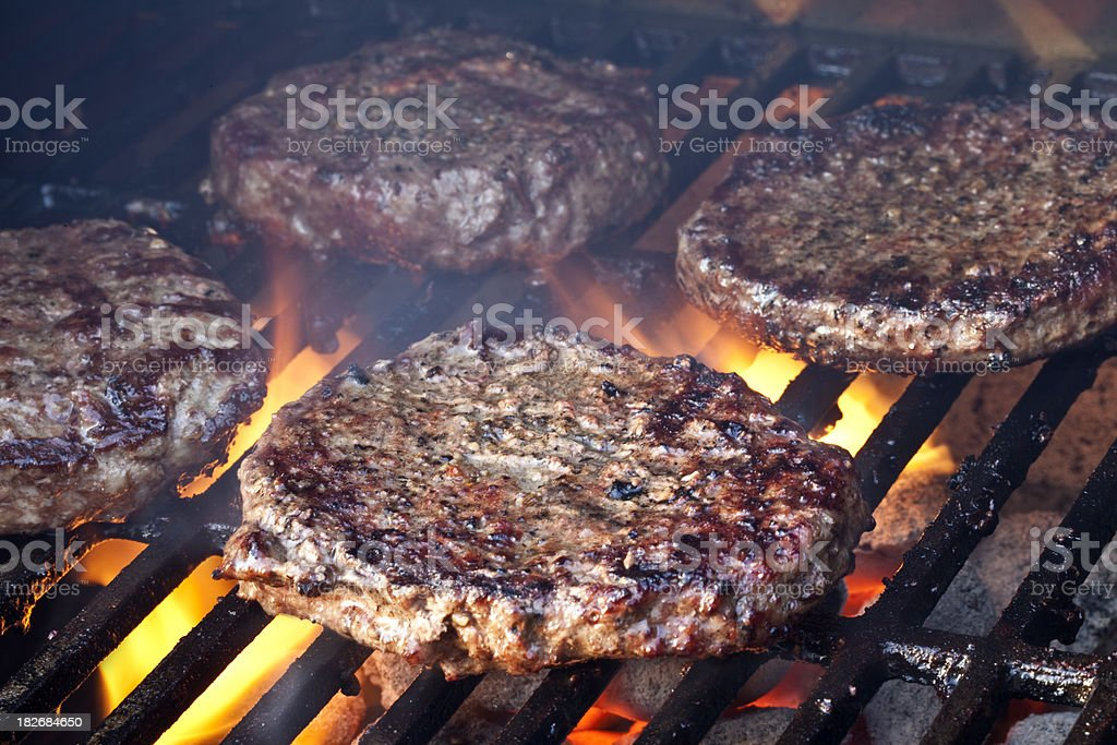 Burgers on a Smokey Charcoal Grill stock photo