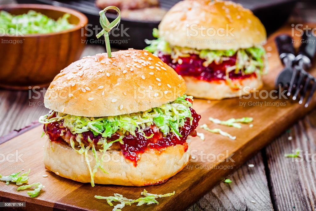 Burgers with a cutlet of turkey, cranberry sauce and salad stock photo