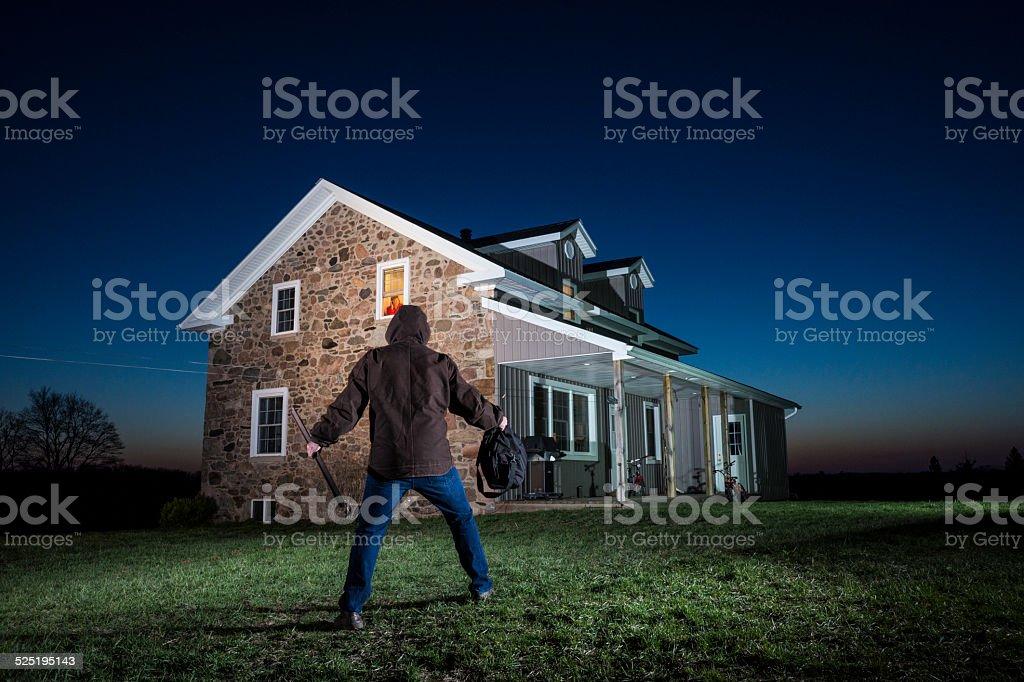 Burglar approaches a house stock photo