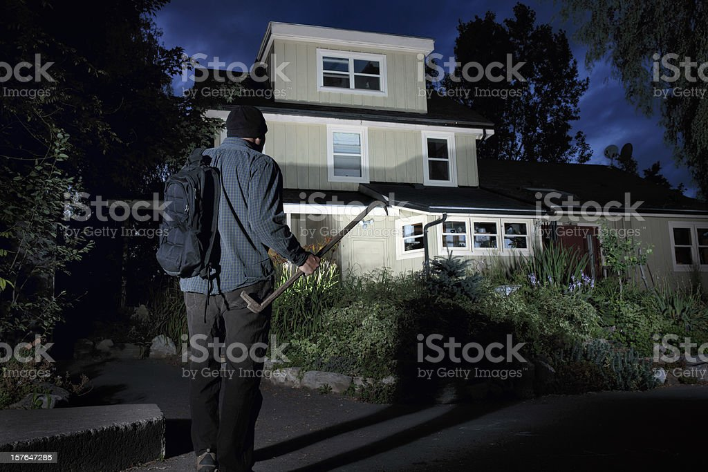 Burglar approaching a home at night stock photo