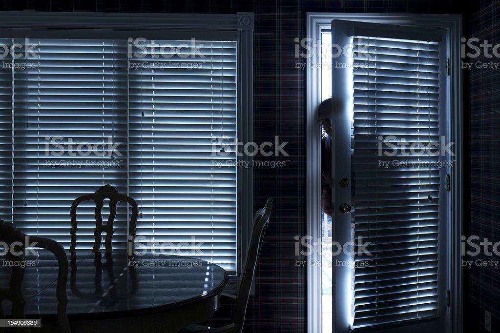 Burglar Breaking In To Home At Night Through Back Door stock photo