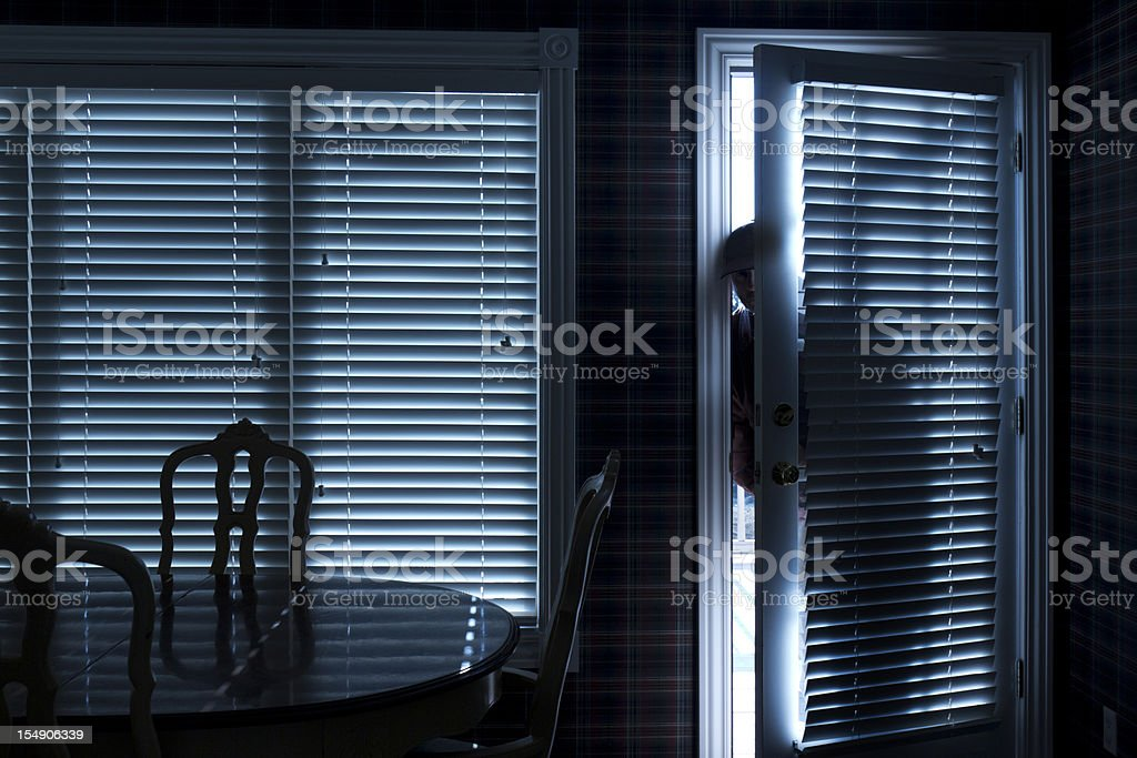 Burglar Breaking In To Home At Night Through Back Door stock photo