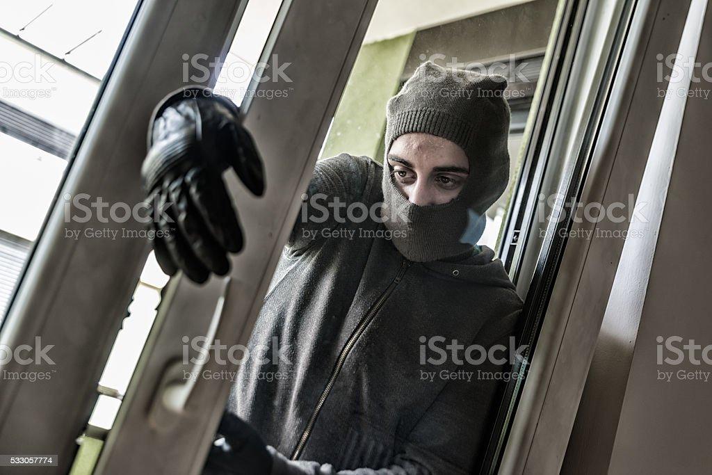 Burglar breaking into a house stock photo