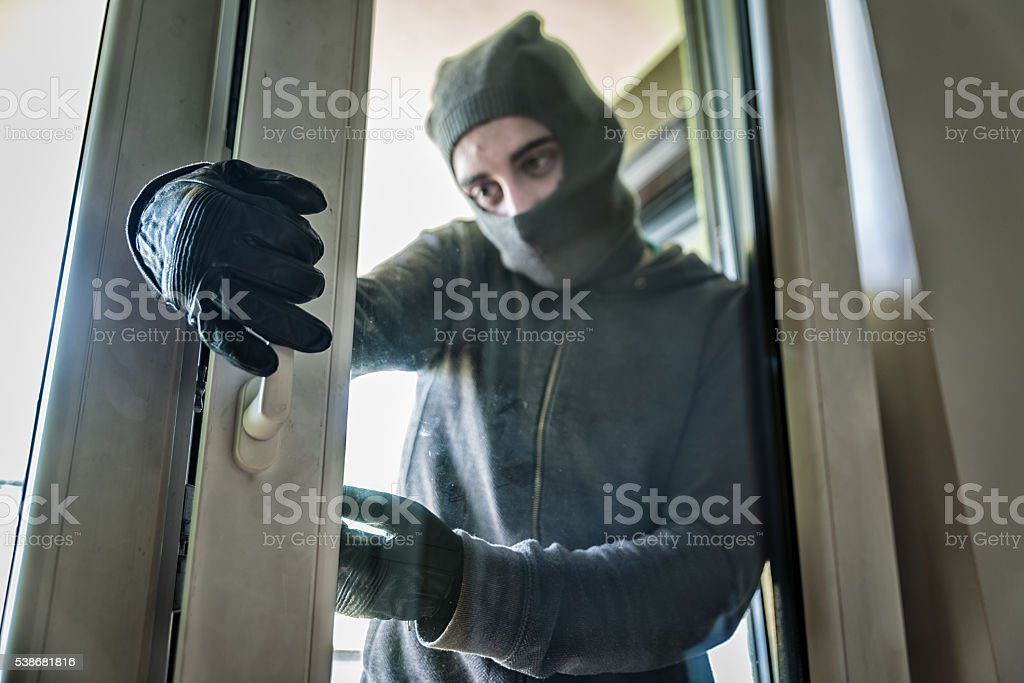 Burglar breaking into a house stock photo