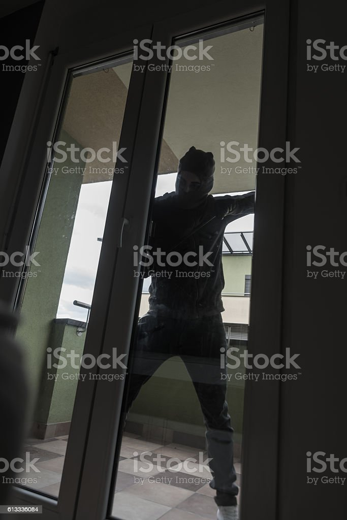Burglar Breaking Into House By Forcing Door With Crowbar stock photo