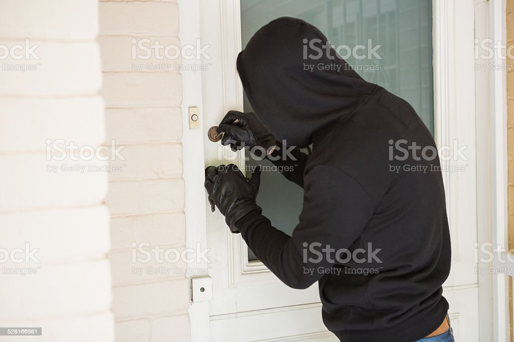 Burglar breaking open the door stock photo