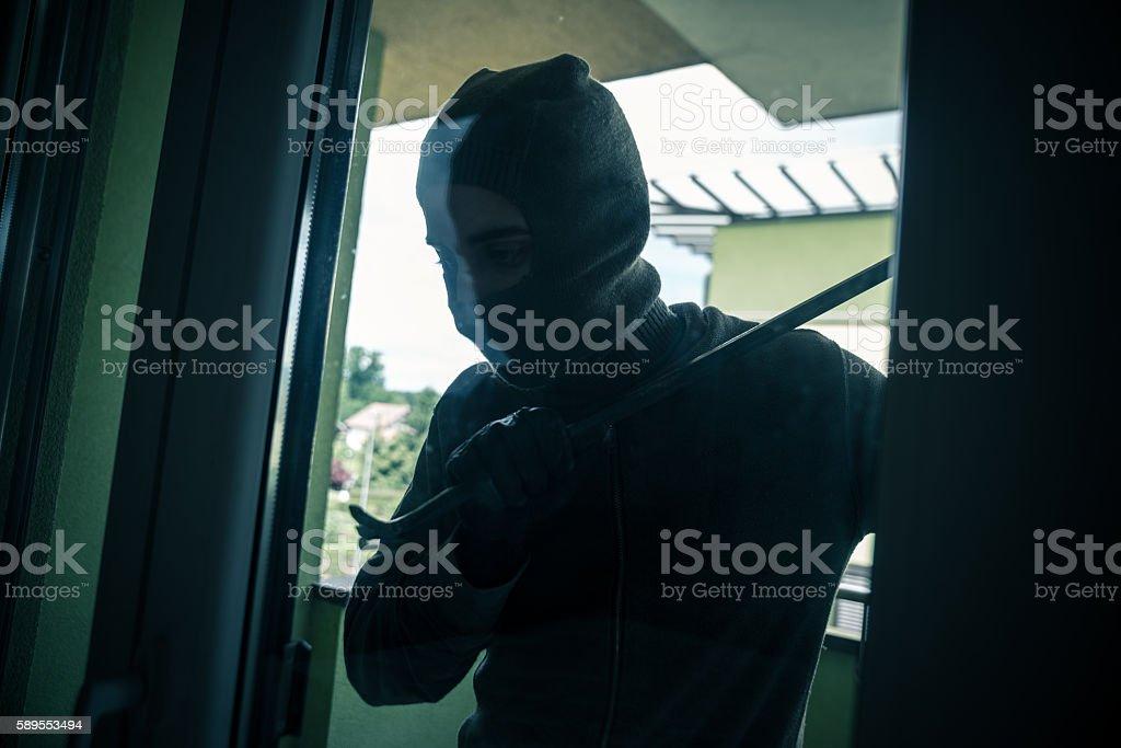 Burglar breaks into a residential building stock photo