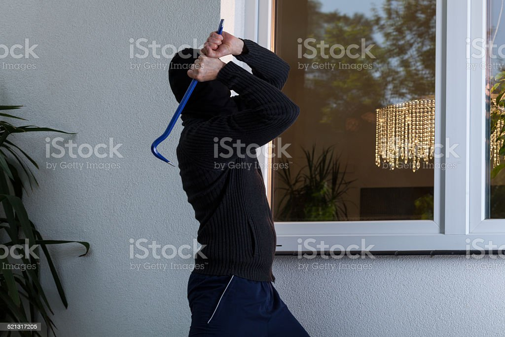Burglar breaks the window stock photo