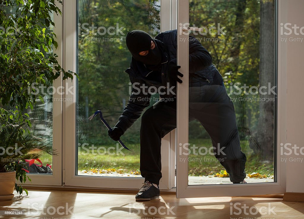 Burglar entering through the balcony window stock photo