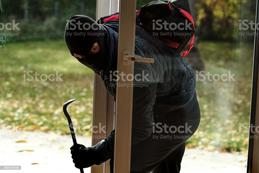 Burglar entering to house stock photo