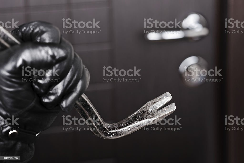 Burglar hand holding crowbar break opening door stock photo