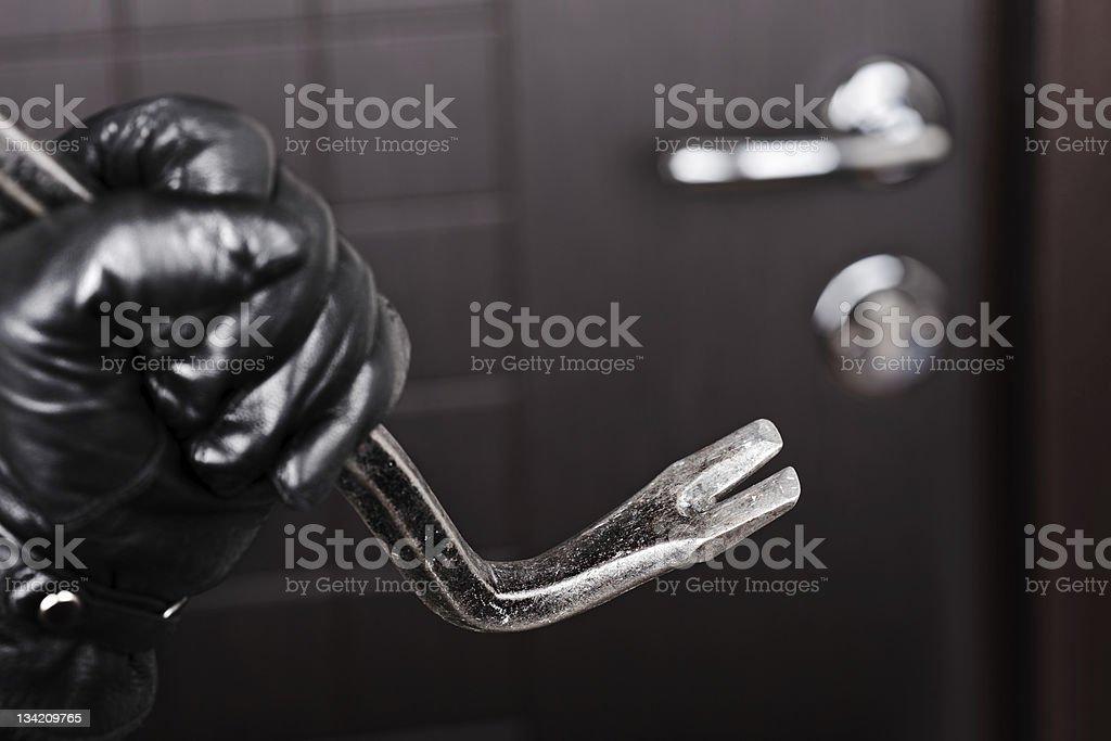 Burglar hand holding crowbar break opening door stock photo