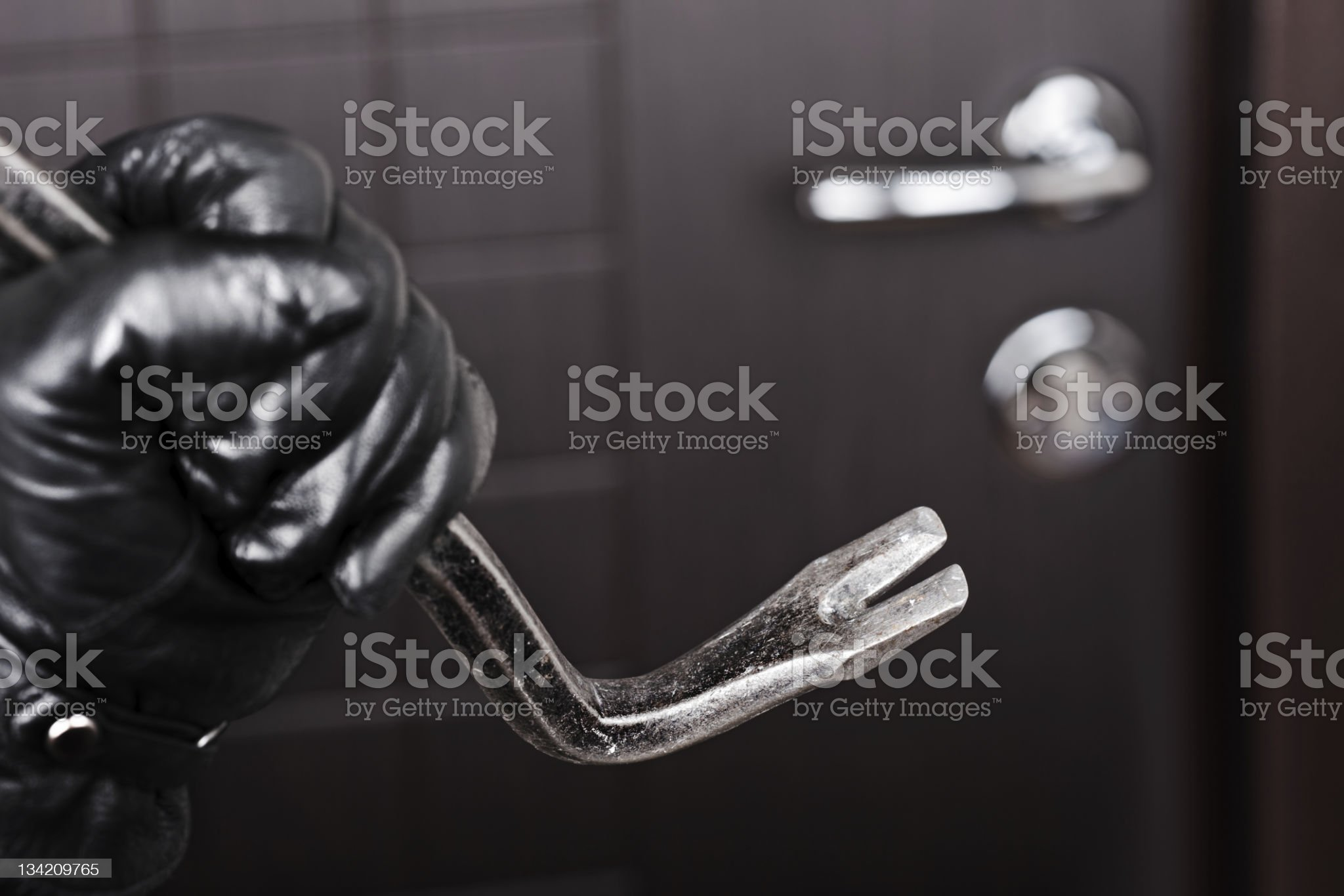 Burglar hand holding crowbar break opening door royalty-free stock photo