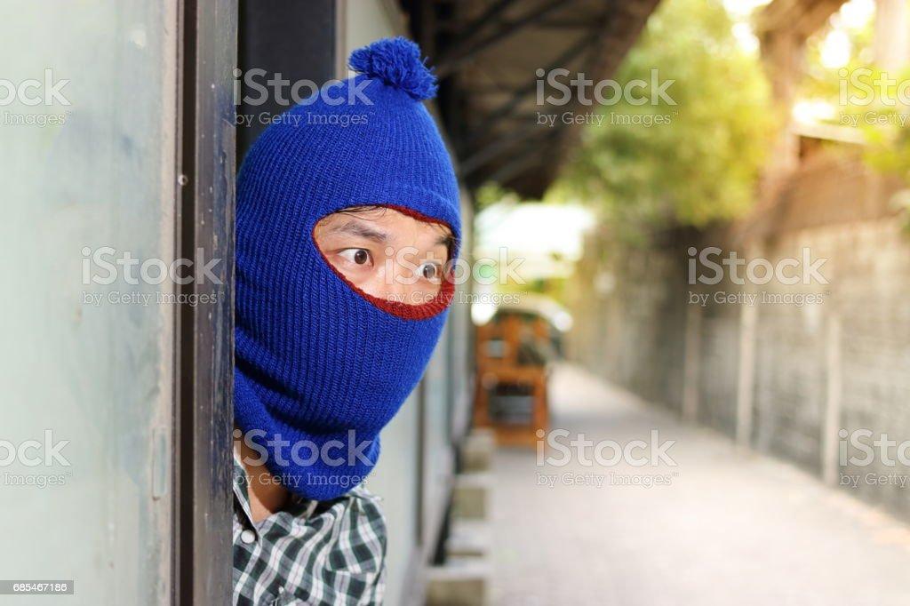 Burglar hiding behind entrance before burglary. Criminal concept stock photo