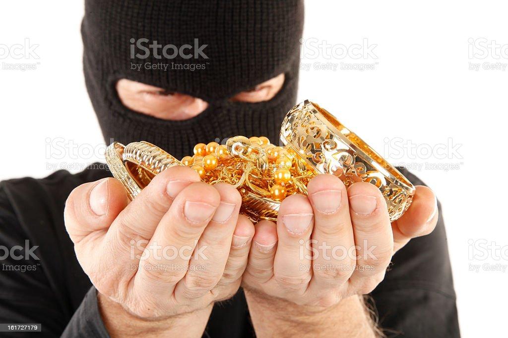 Burglar in black mask holds stolen golden loot in hands royalty-free stock photo