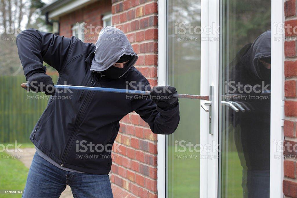A burglar in black trying to break into a glass door stock photo