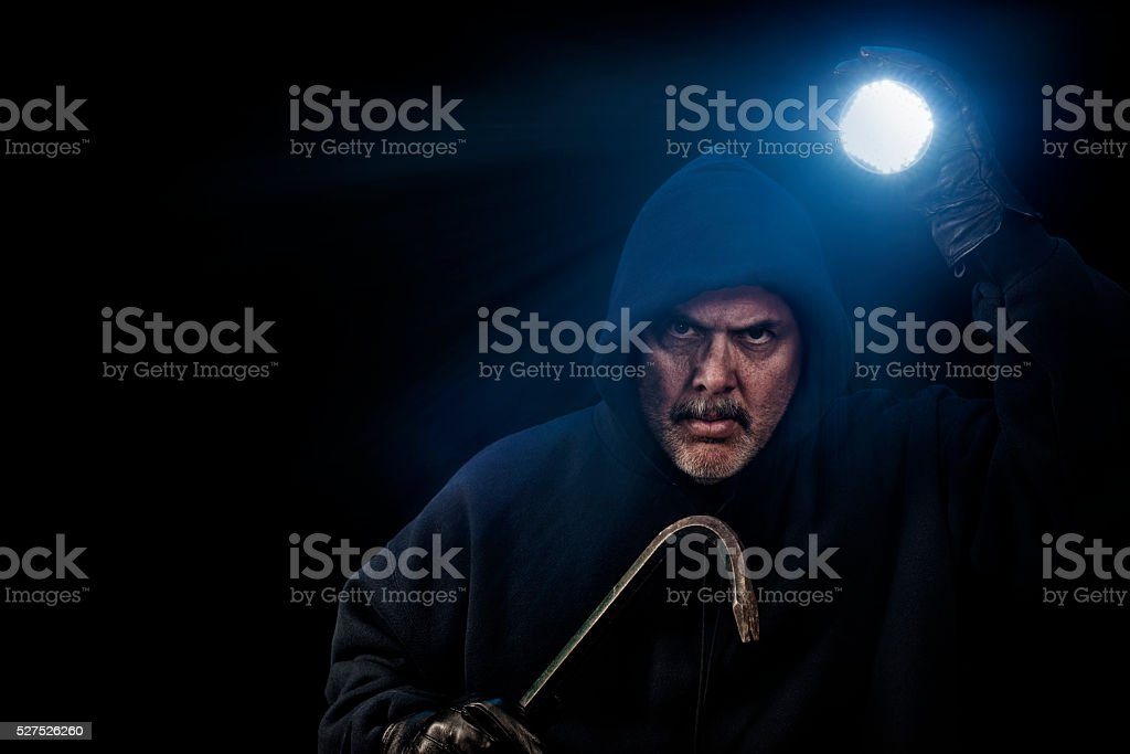Burglar in dark hoodie with crowbar and flashlight stock photo