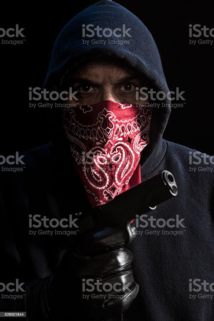 Burglar in dark hoodie with hand gun stock photo