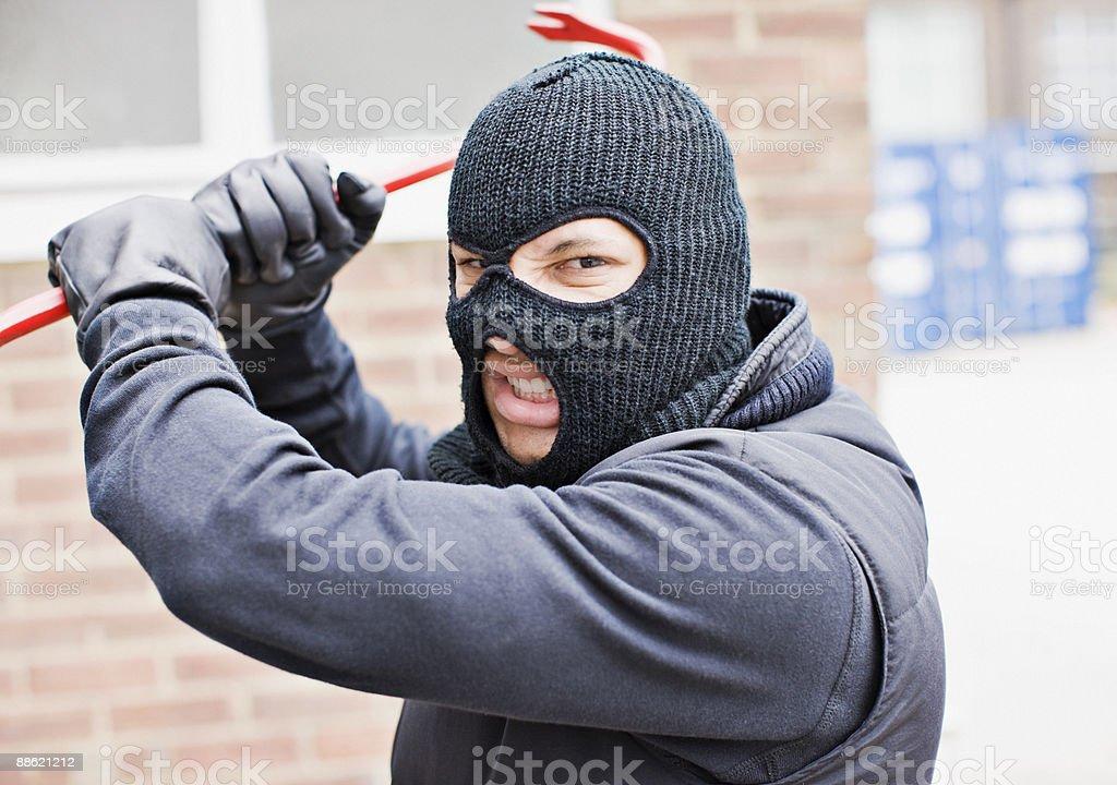 Burglar in ski mask wielding crowbar royalty-free stock photo