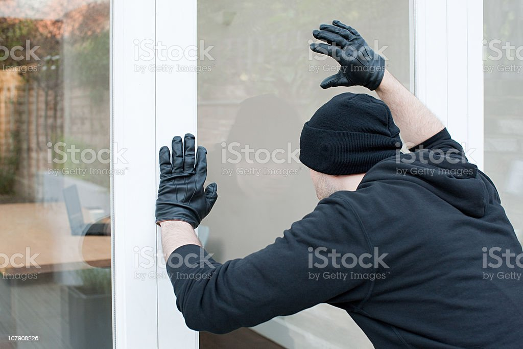Burglar looking through window stock photo