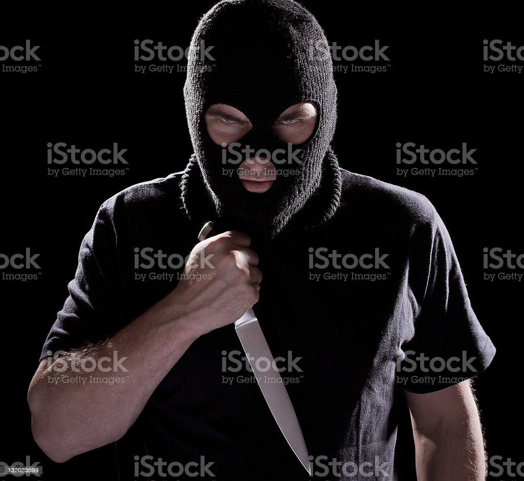 Burglar, man in mask holding knife stock photo