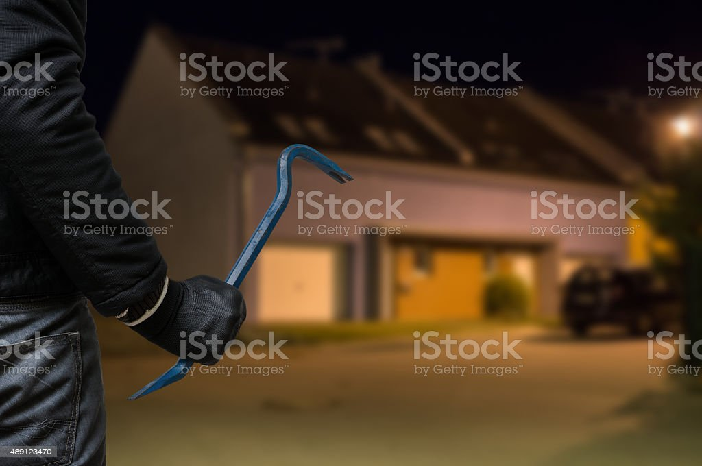 Burglar or robber with crowbar stands in front of house stock photo